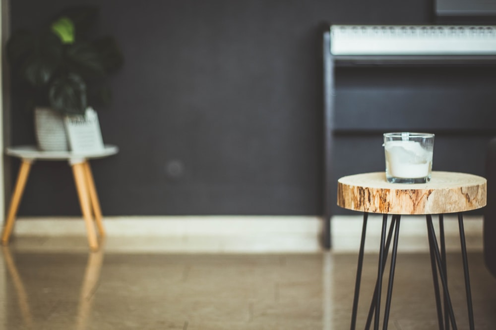 focus photography of white candle on brown wood slab end table inside room