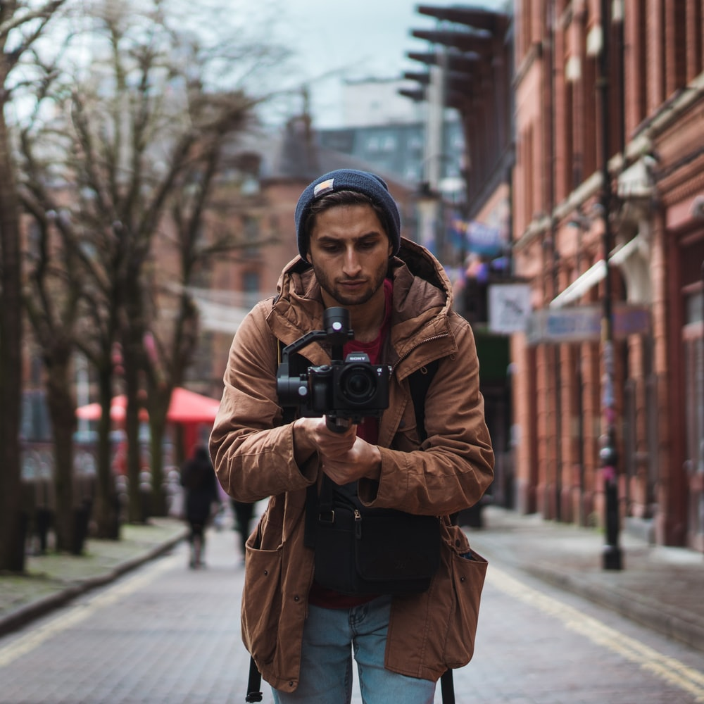 depth of field photography of man holding camera