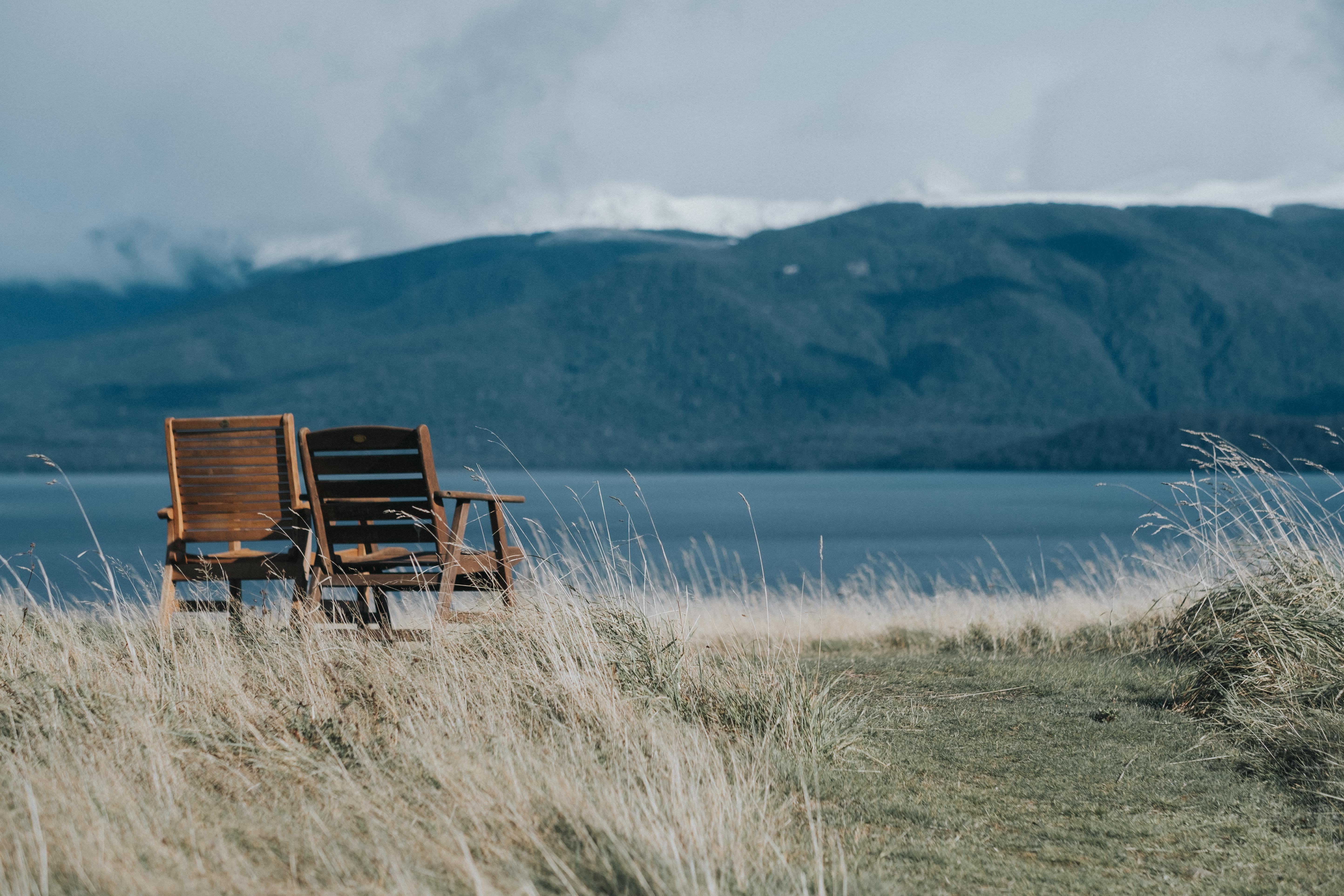 two brown wooden armchairs in front of body of water