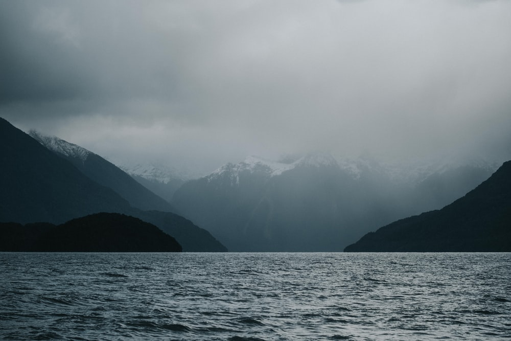 fog-covered mountain near body of water