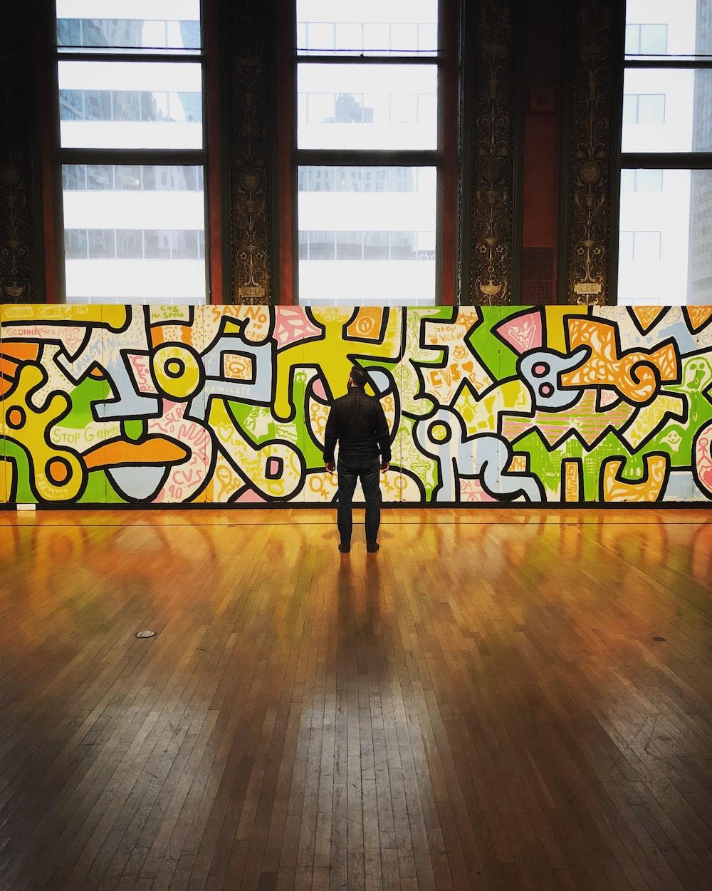 man wearing black jacket and pants facing multicolored graffiti