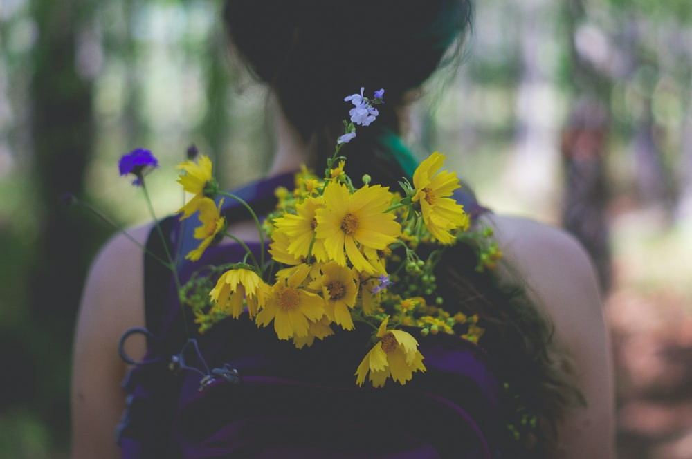 person wearing backpack with yellow petaled flower