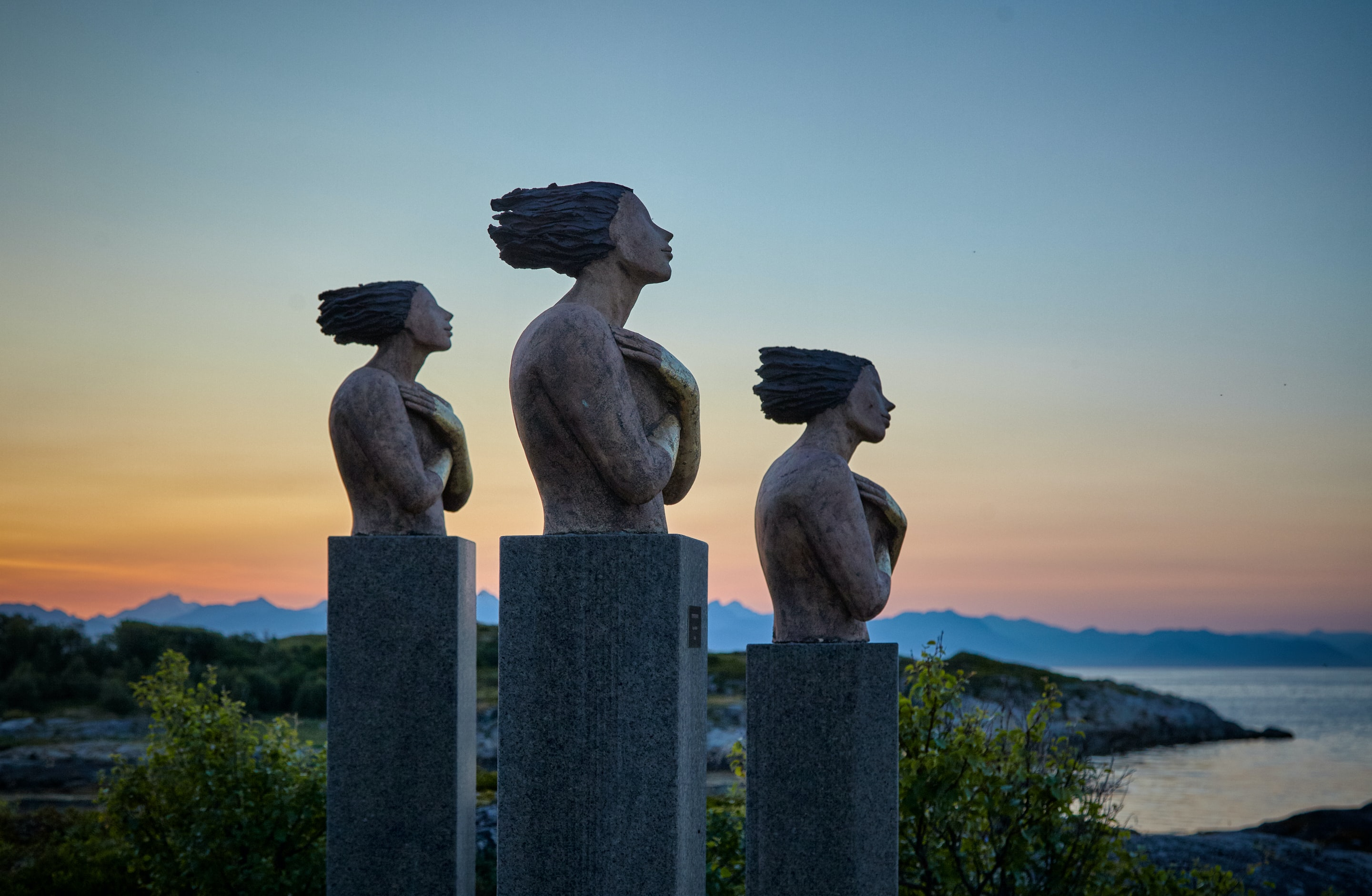 three concrete statues