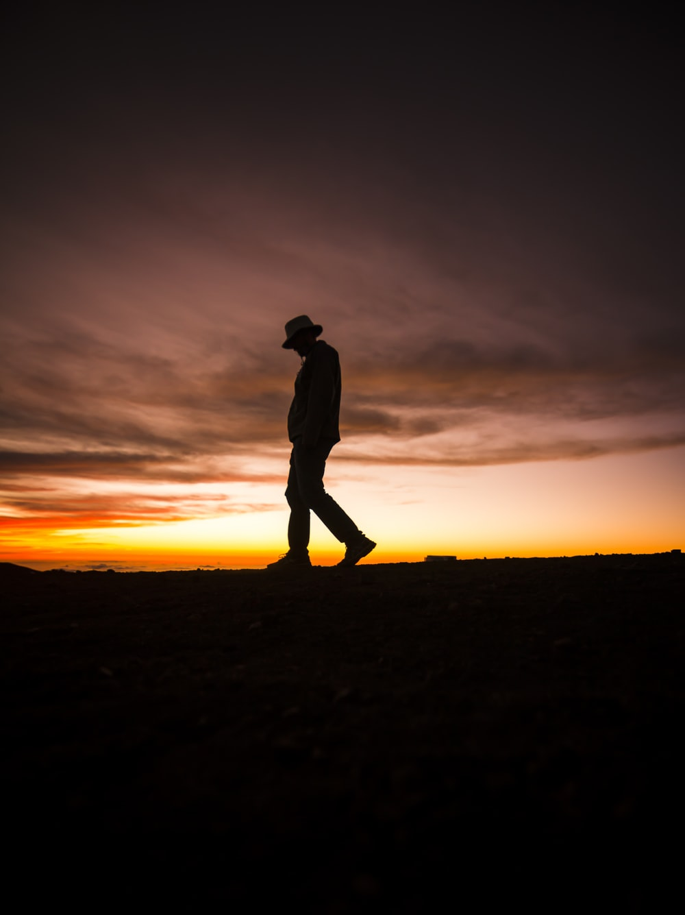 silhouette photography of man wearing fedora hat