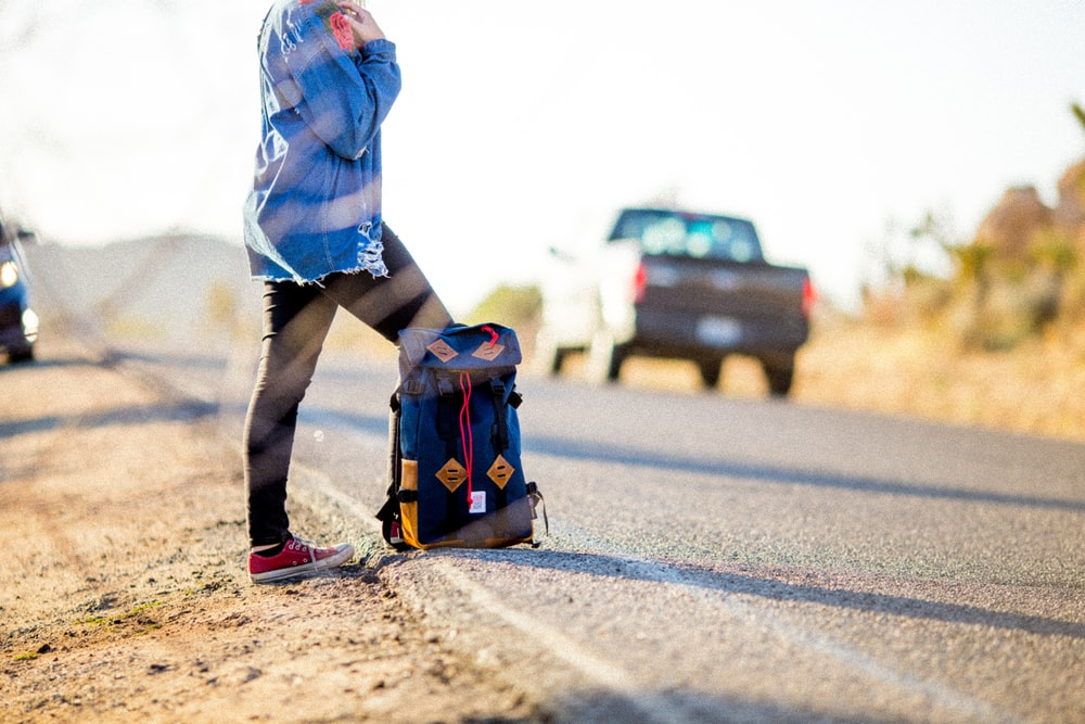 black and blue backpack on road, hitch hiking to travel on a budget