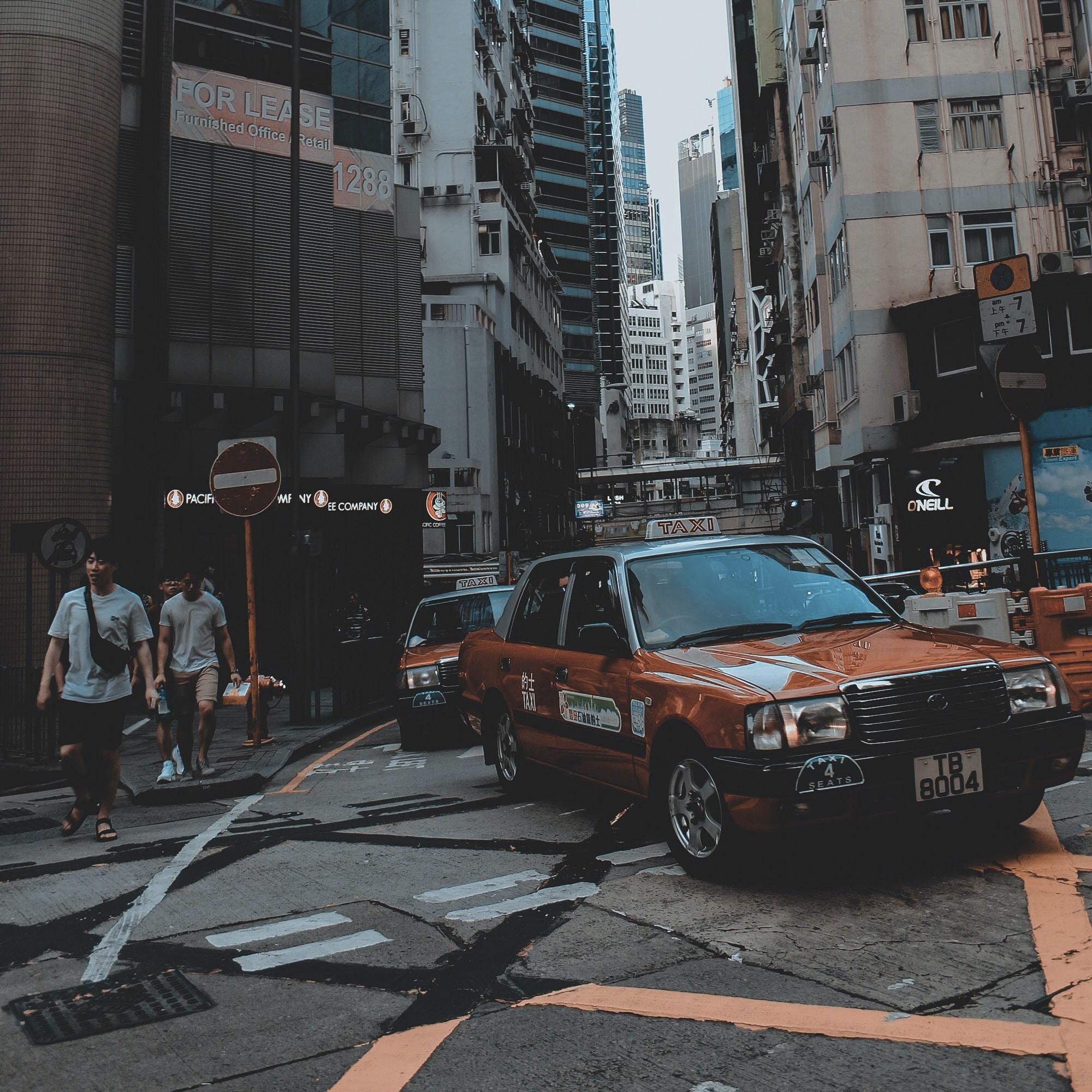 brown car beside man walking in street during daytime