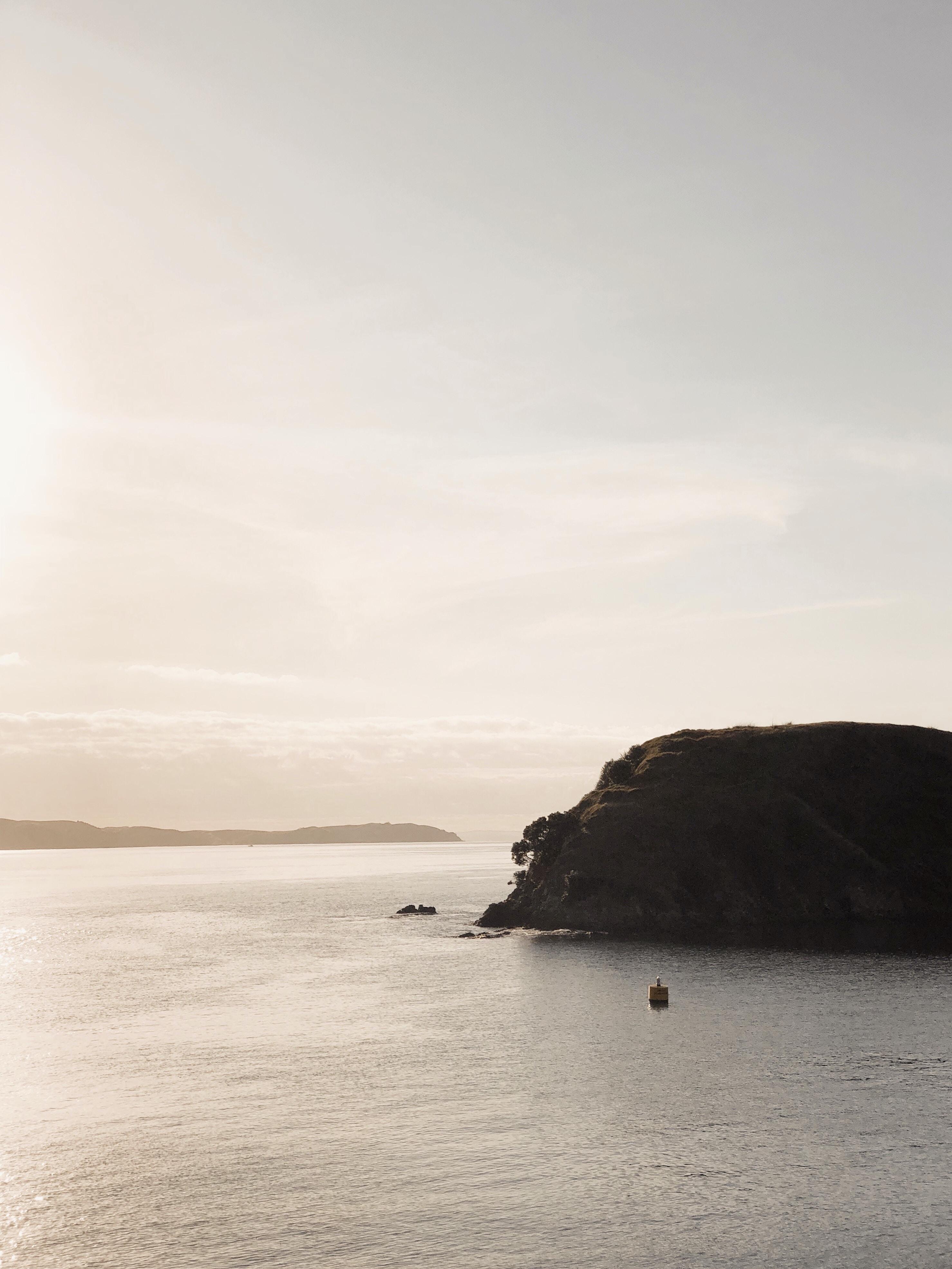 boat sailing near rock of ocean