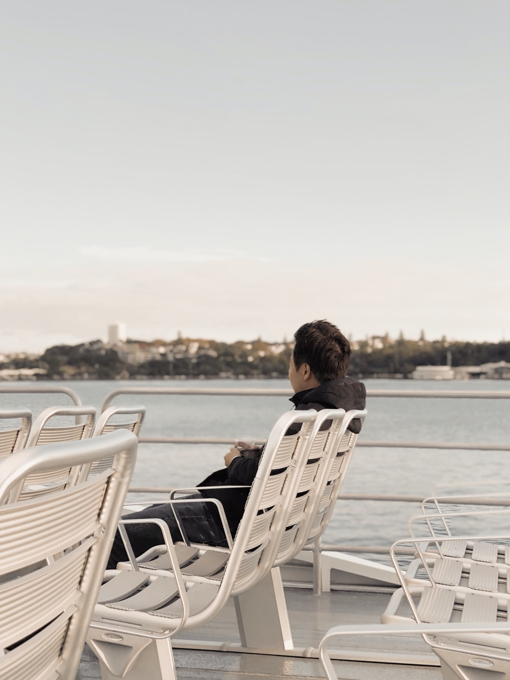 man sitting on chair under cloudy skies