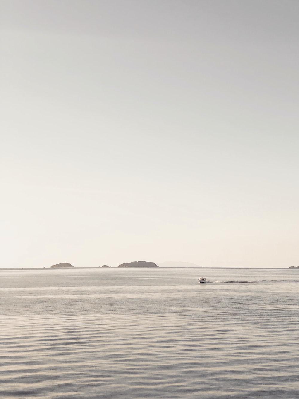 boat on sea under gray sky