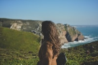 woman looking at cliffs while ocean waves are pounding it during daytime