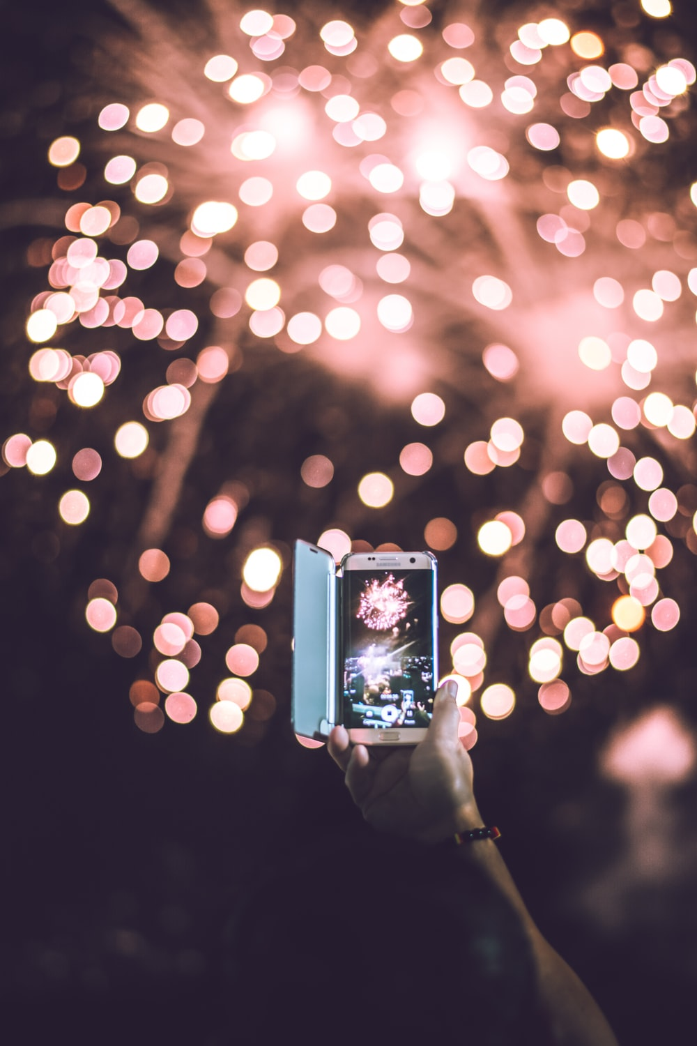 person taking video of pink firework display