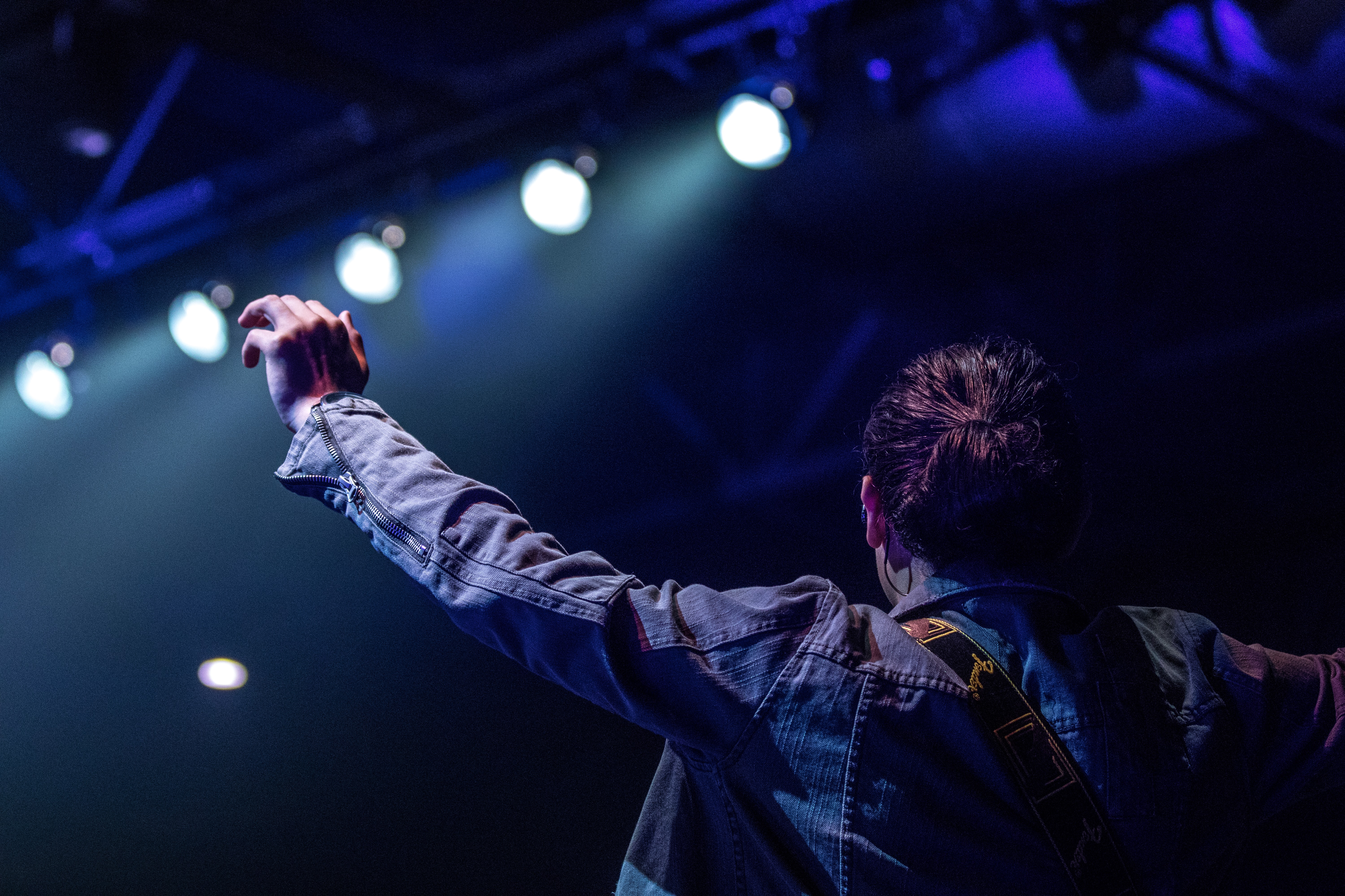 selective focus photography of person on stage with lights