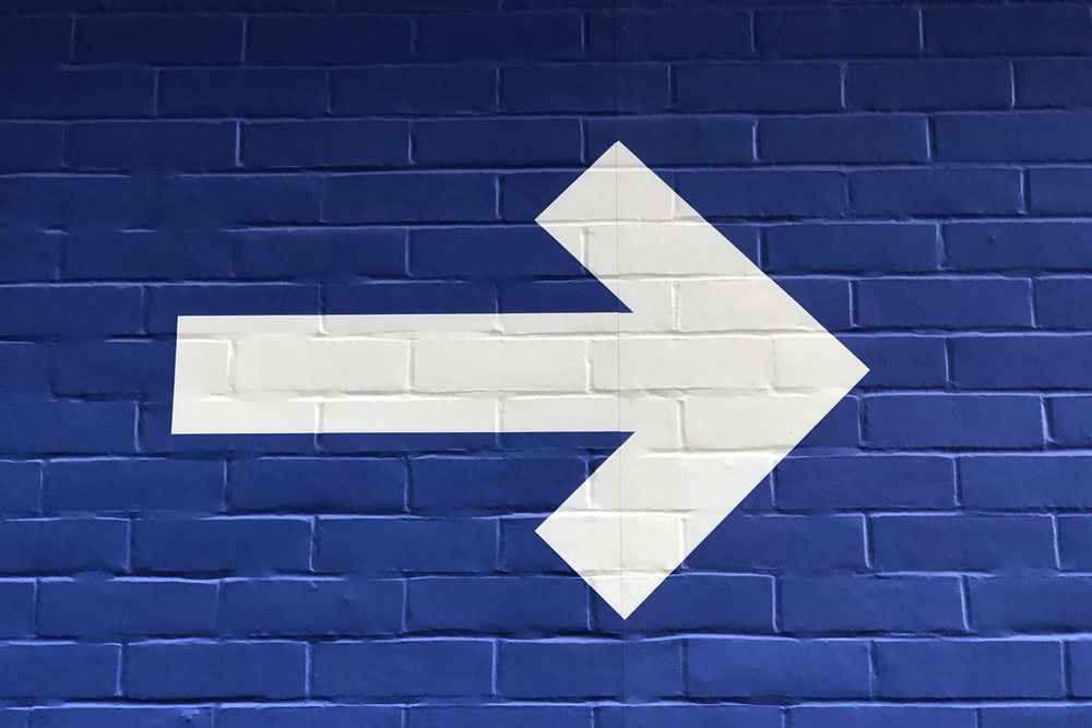 white arrow painted on brick wall