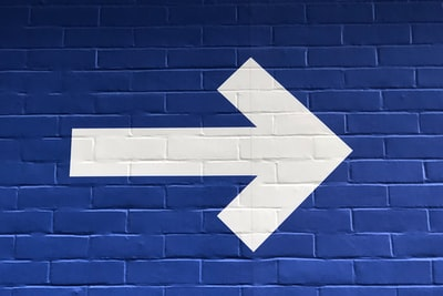 white arrow painted on brick wall right zoom background