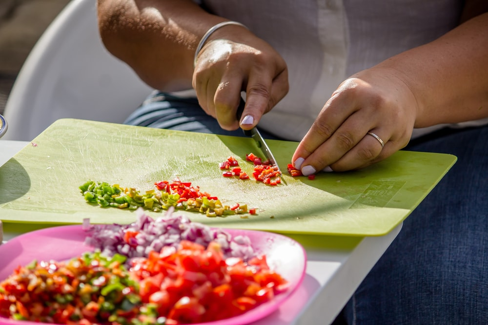 person slicing species on green chopping board