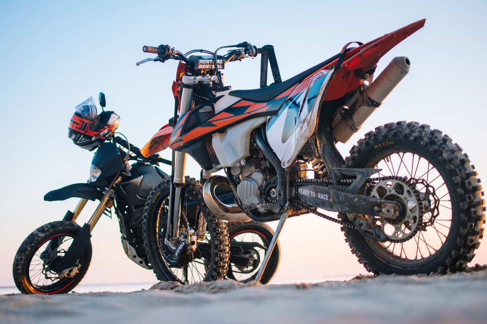 selective focus photography of two white and black dual-sport motorcycles