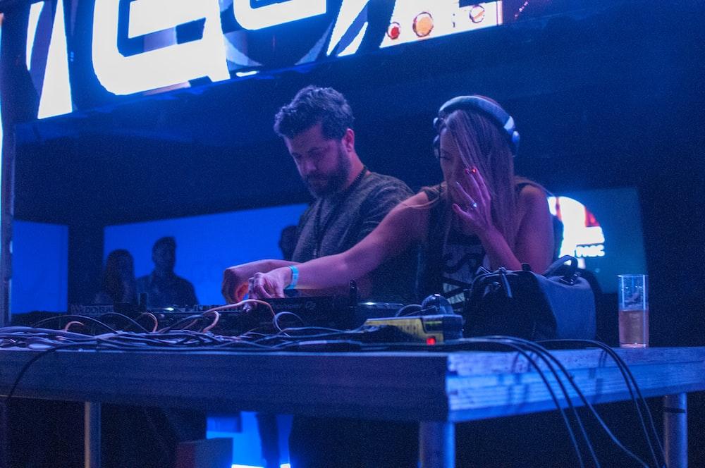 woman playing DJ controller beside man in gray shirt