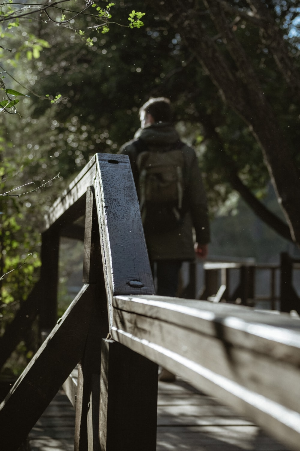 man standing on brown wooden bridge during daytime