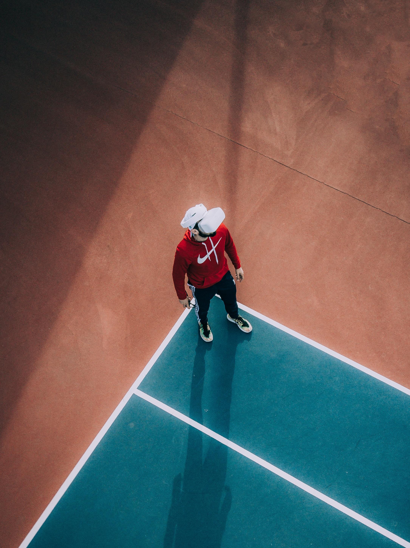 man standing on lawn tennis court