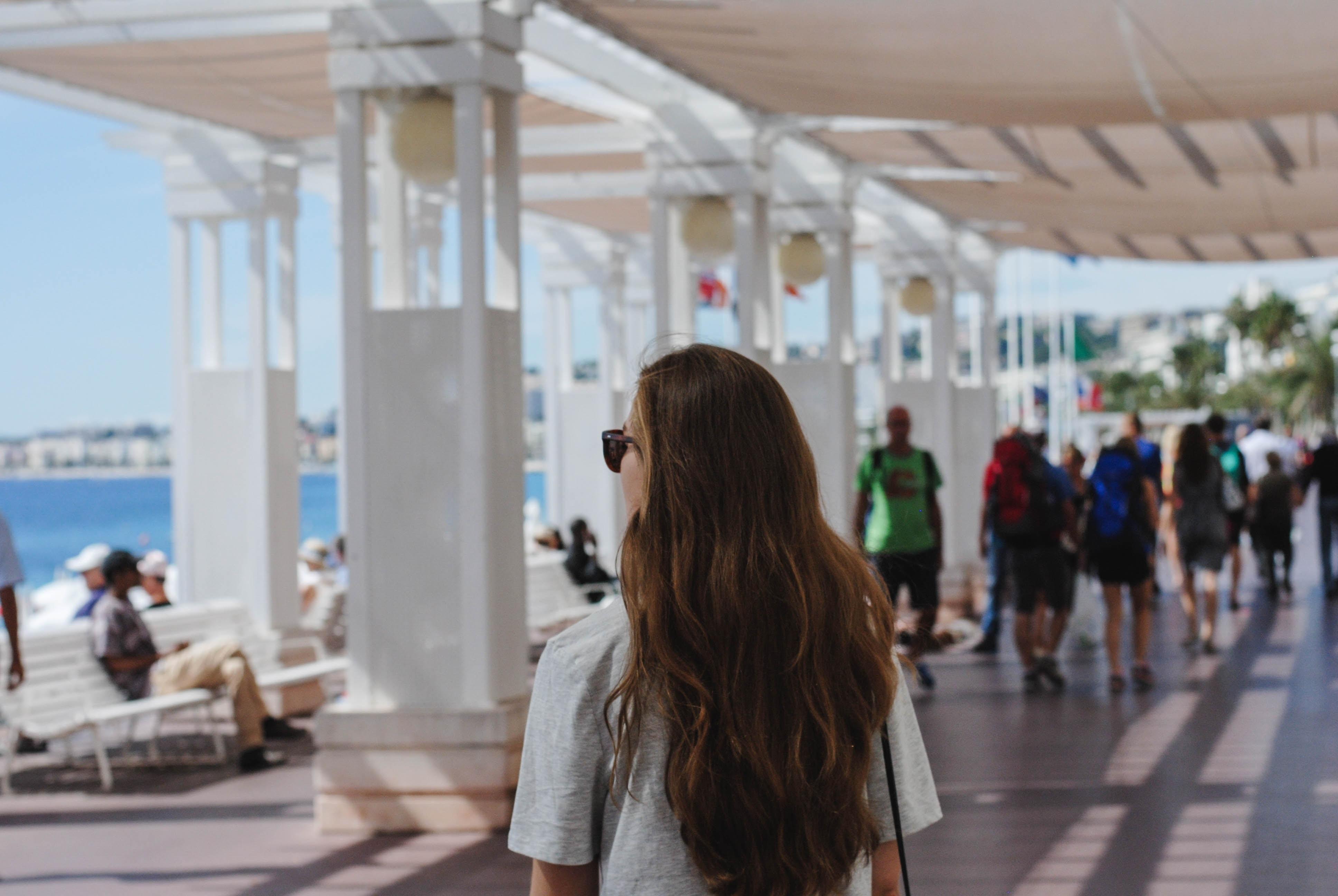 woman standing near white concrete post