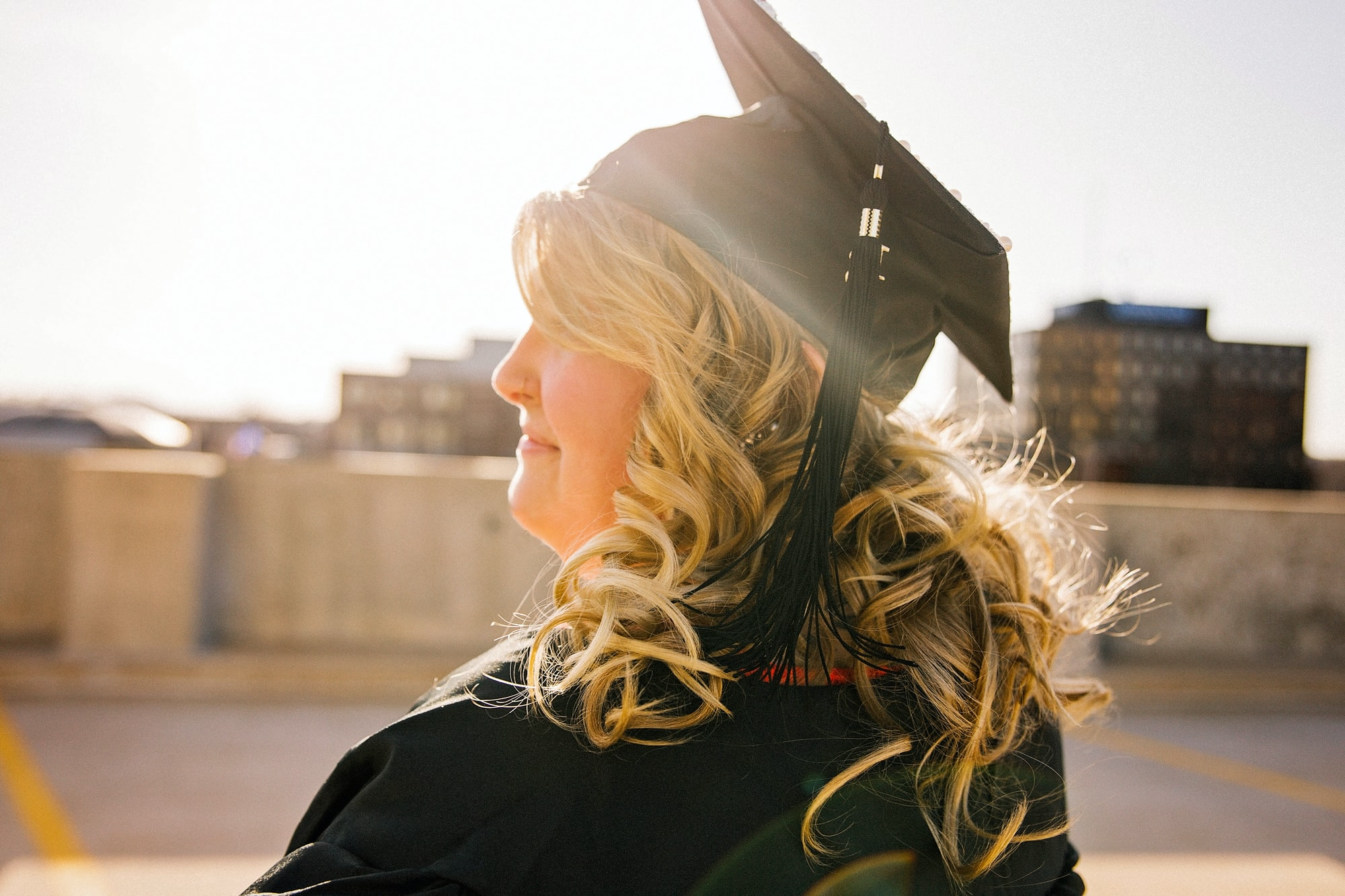A student on her graduation day looking into the sunset.