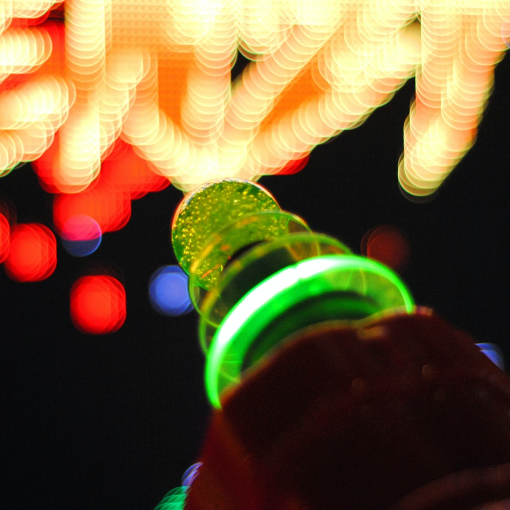 person holding green glass bottle