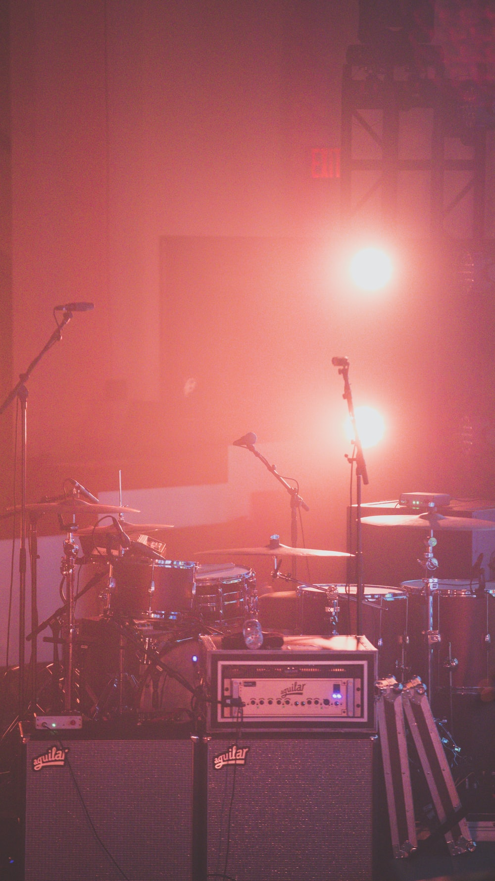 red drum set besides microphone stands
