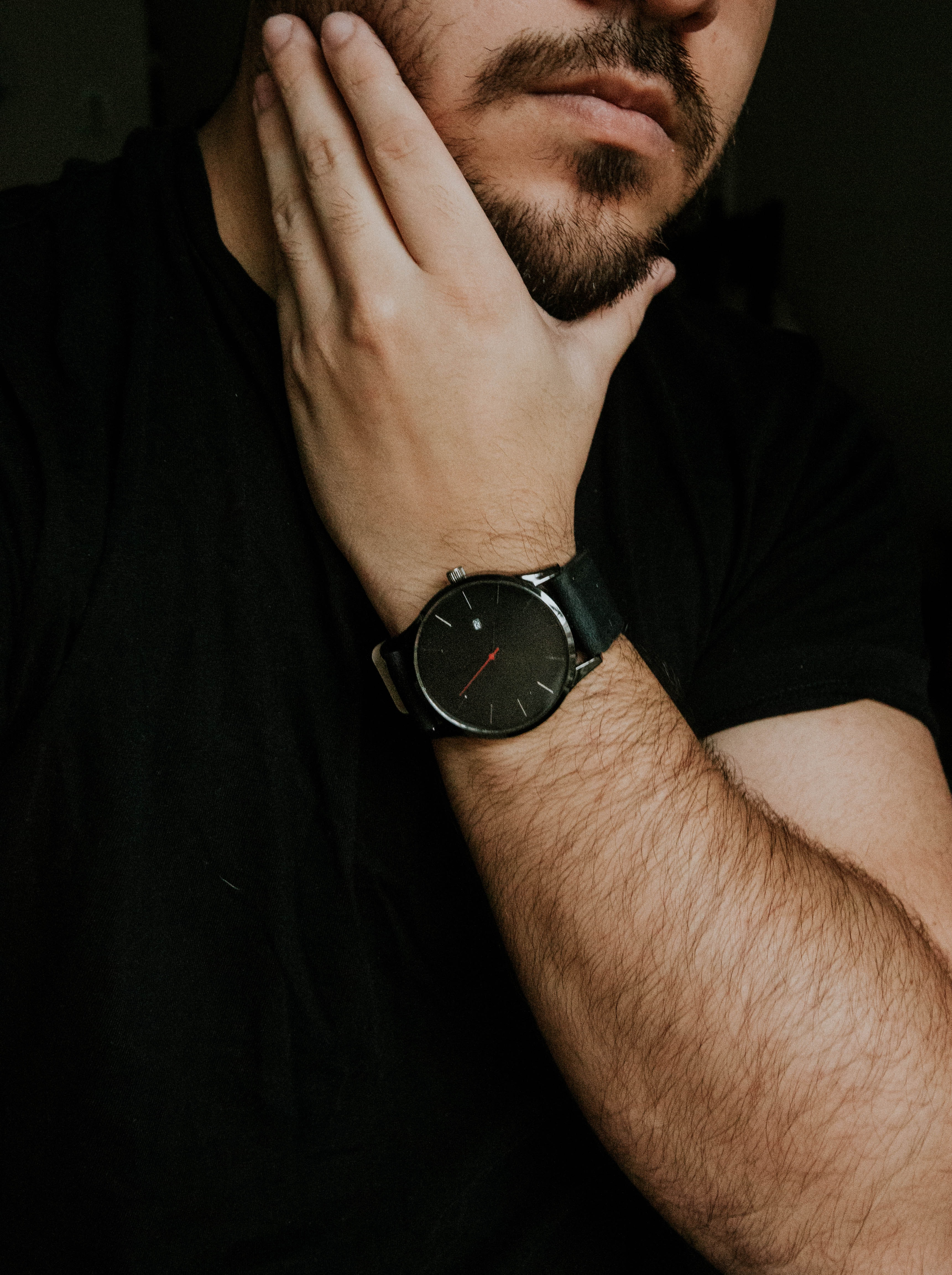 man wearing silver-colored watch holding fave