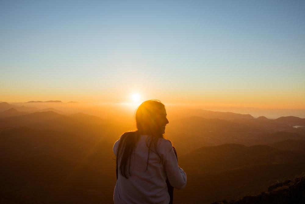 woman sitting while facing sunset