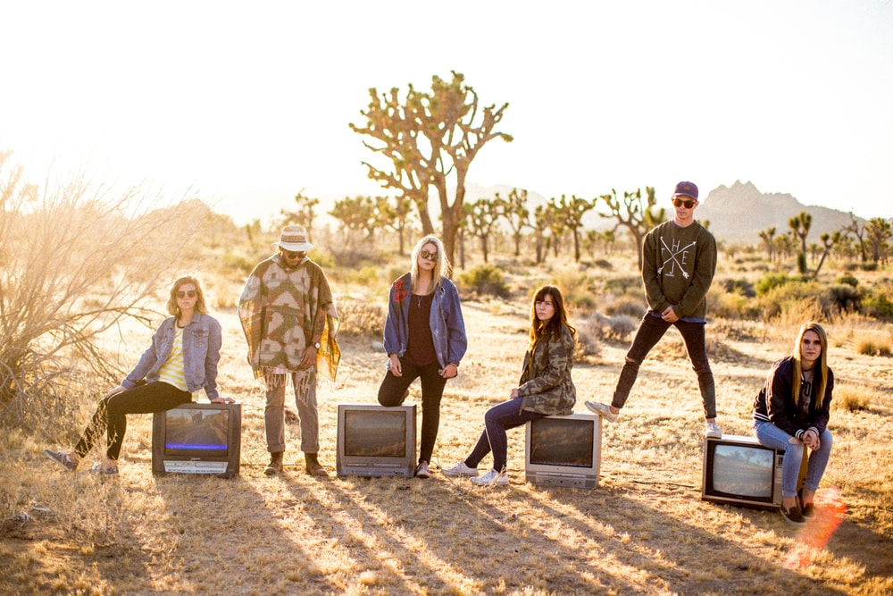 group of six people standing on desert
