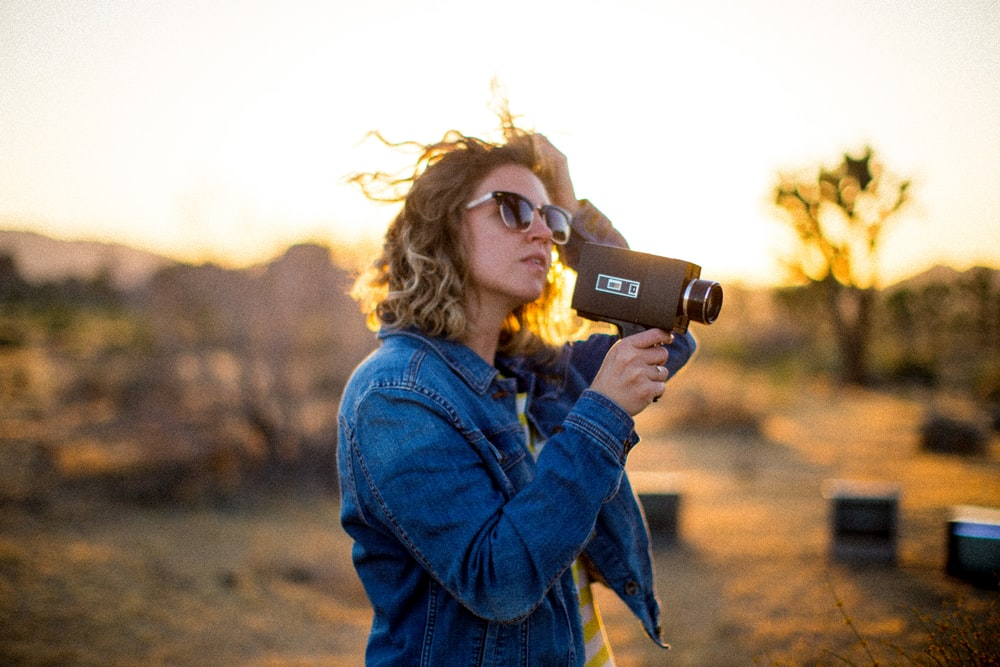 woman holding camera during golden hour