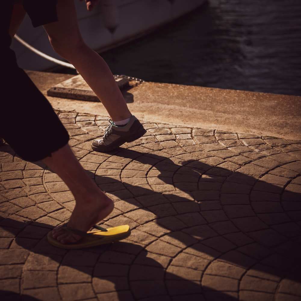 two persons wear slippers and shoes run near harbor