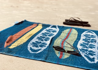 black sunglasses on blue towel beside pair of black flip-flops