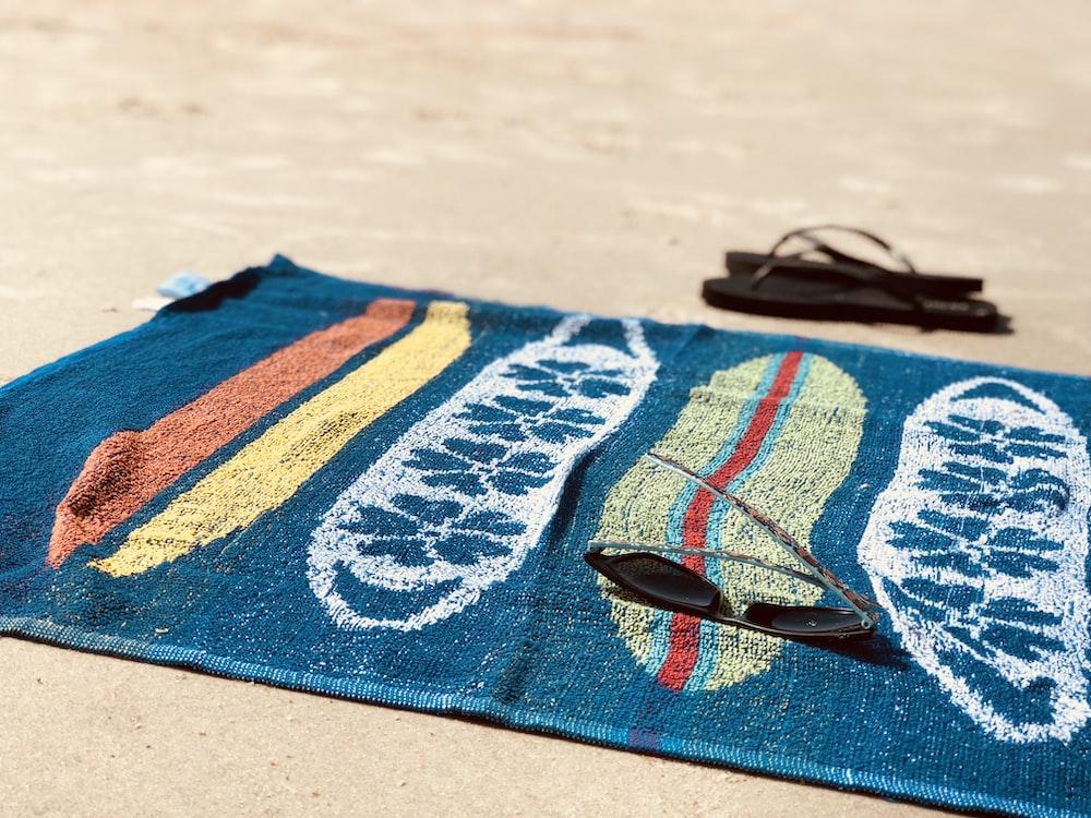 black sunglasses on blue towel beside pair of black flip-flops
