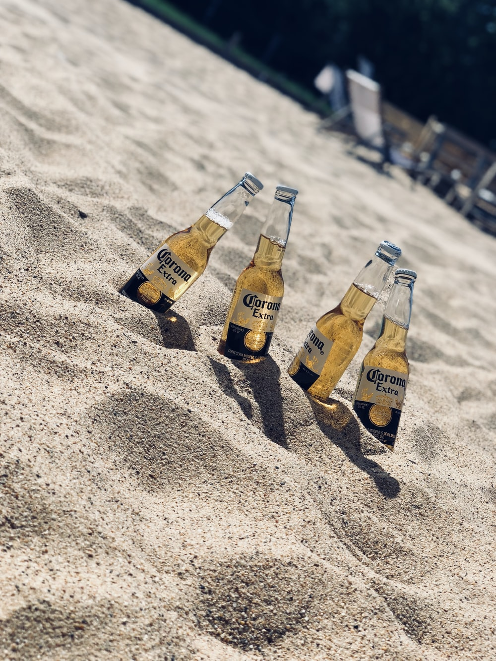 four Corona Extra beer bottles in sand