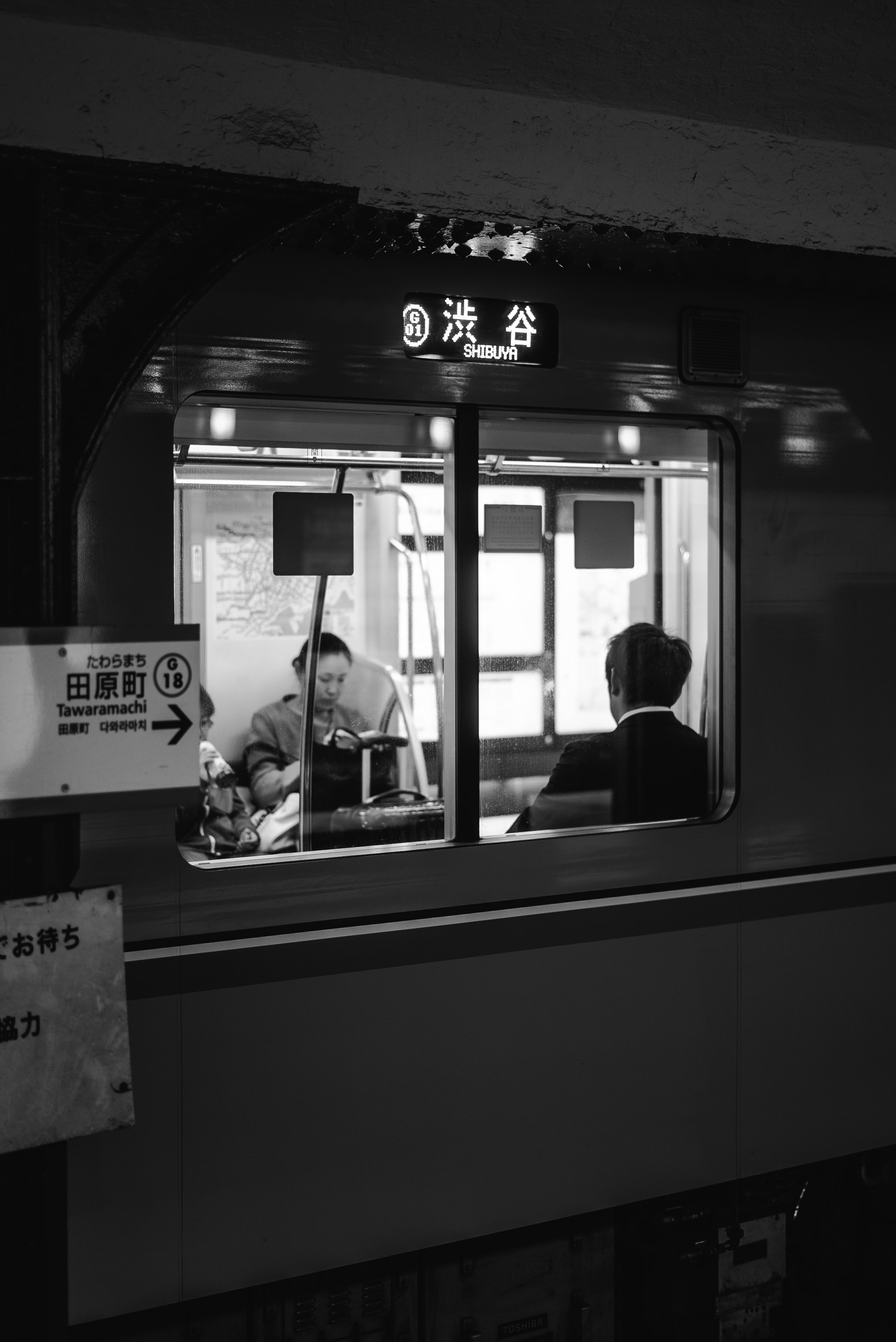 grayscale photo of two people sitting in train