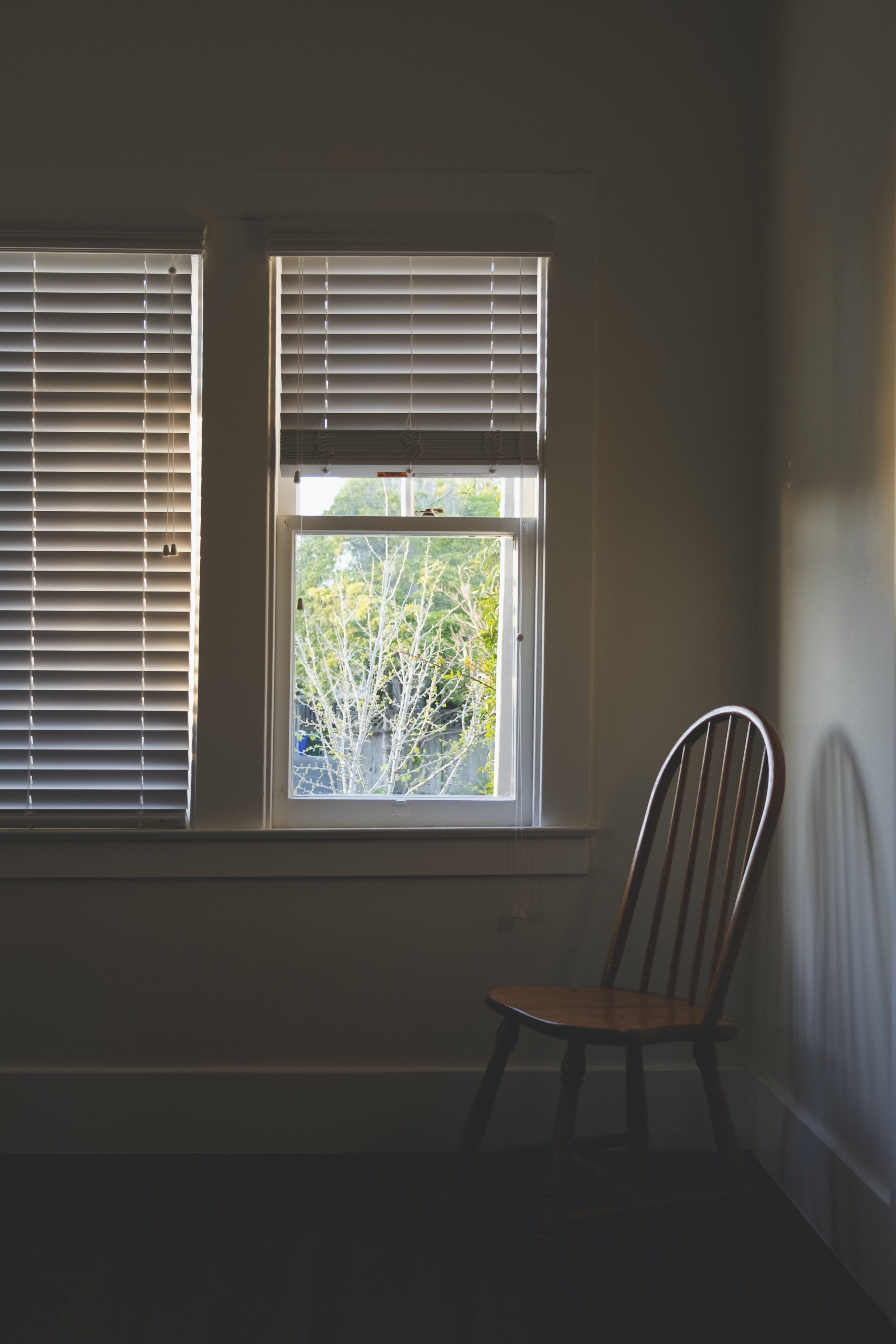 brown wooden chair beside clear glass window