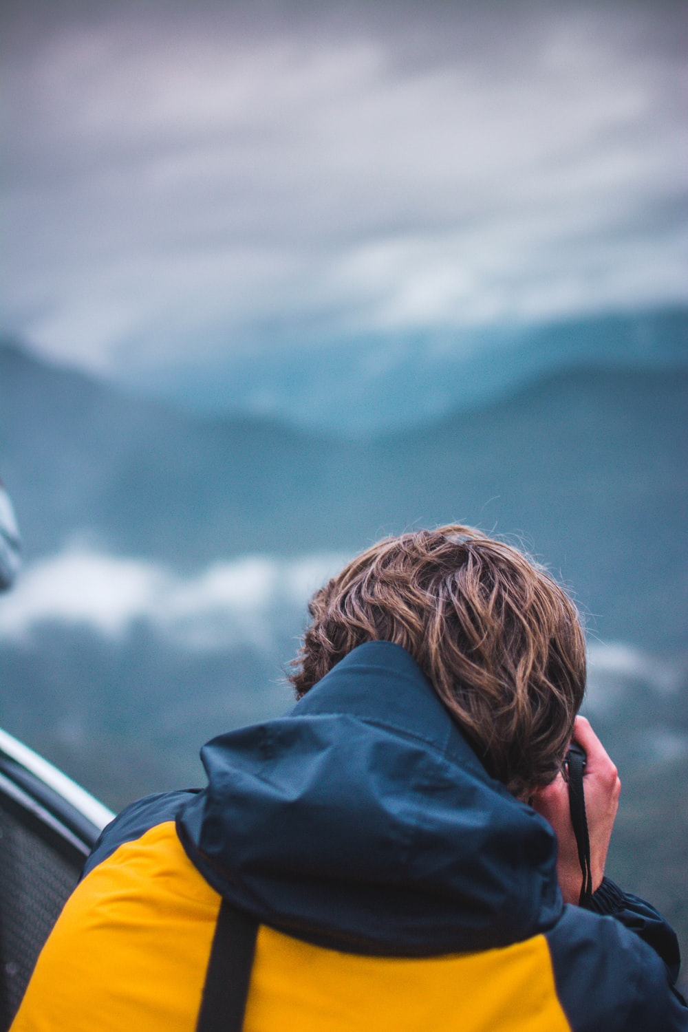 selective focus photography of person taking photo of mountain at daytime
