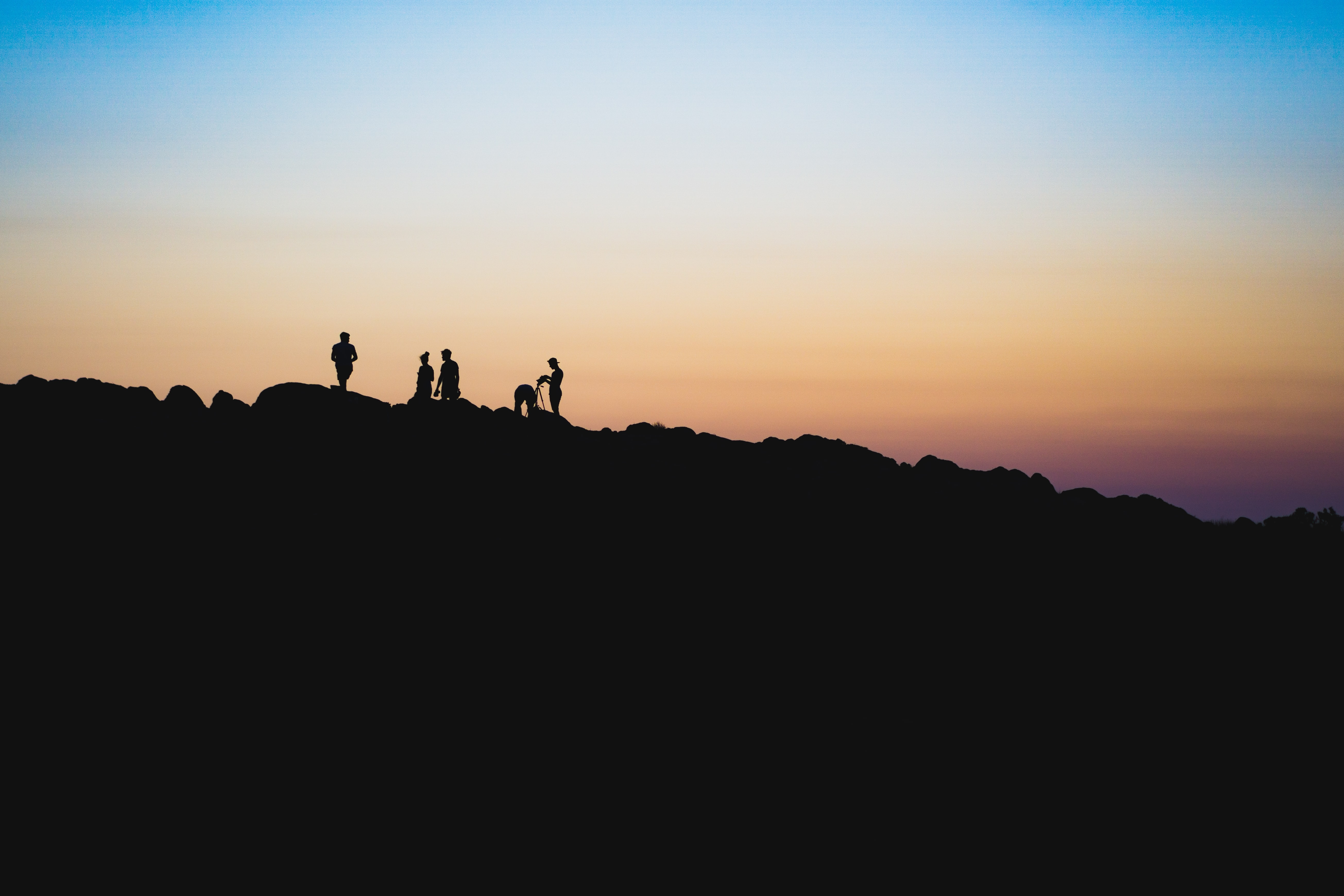 silhouette of people on a mountain