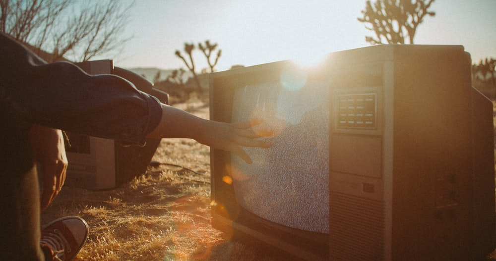 person touching CRT TV screen