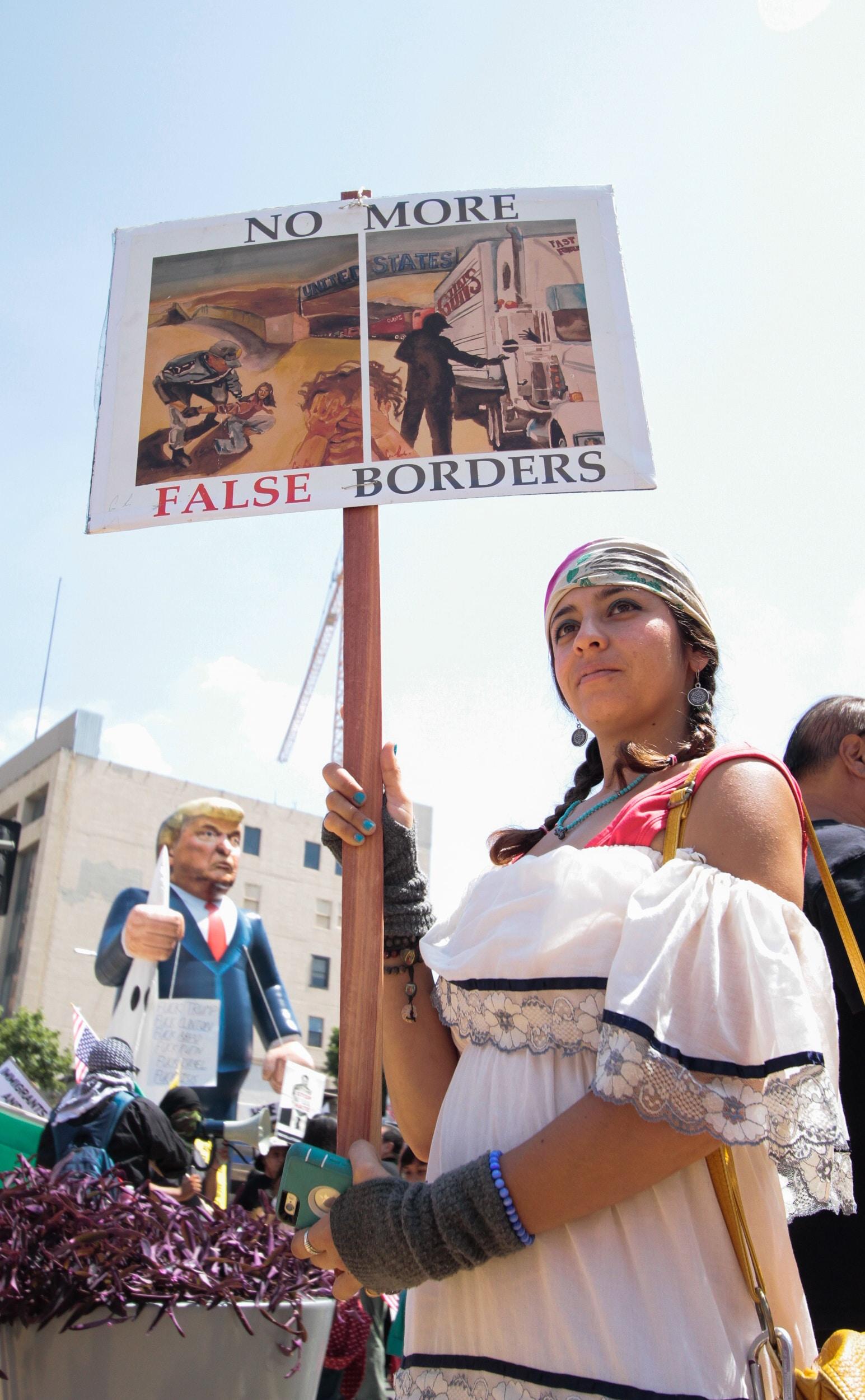 woman protesting holding no more false borders-printed board signage