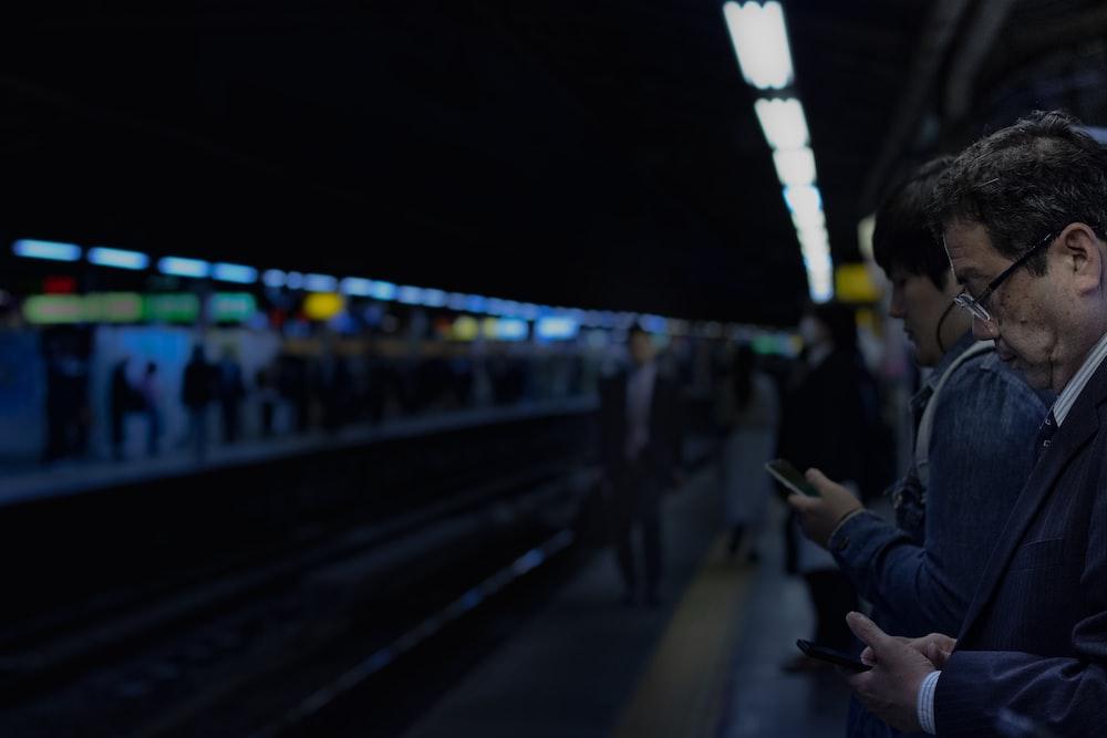 man waiting for train white holding cellphone
