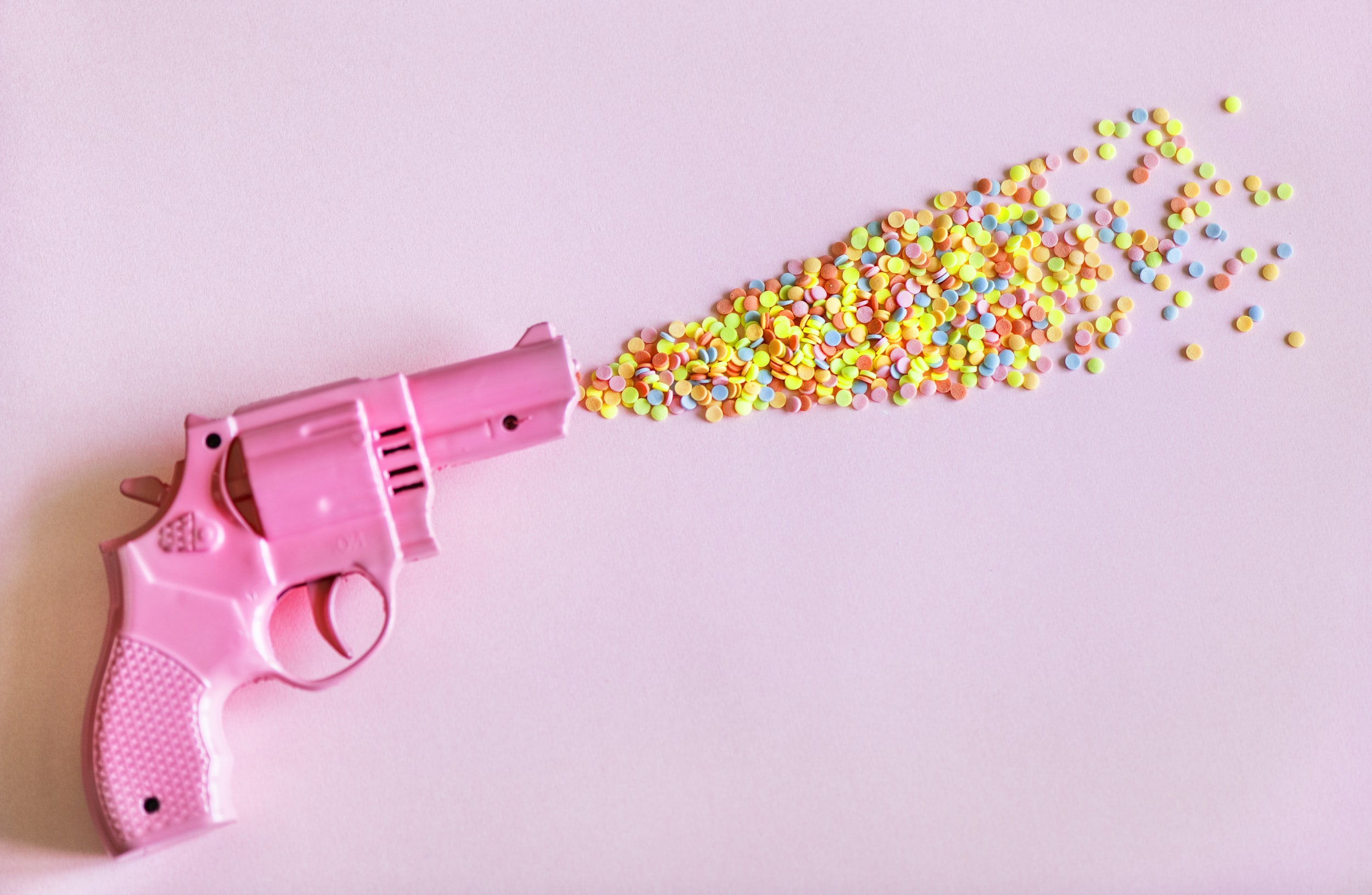 pink revolver pistol with multicolored blast photography