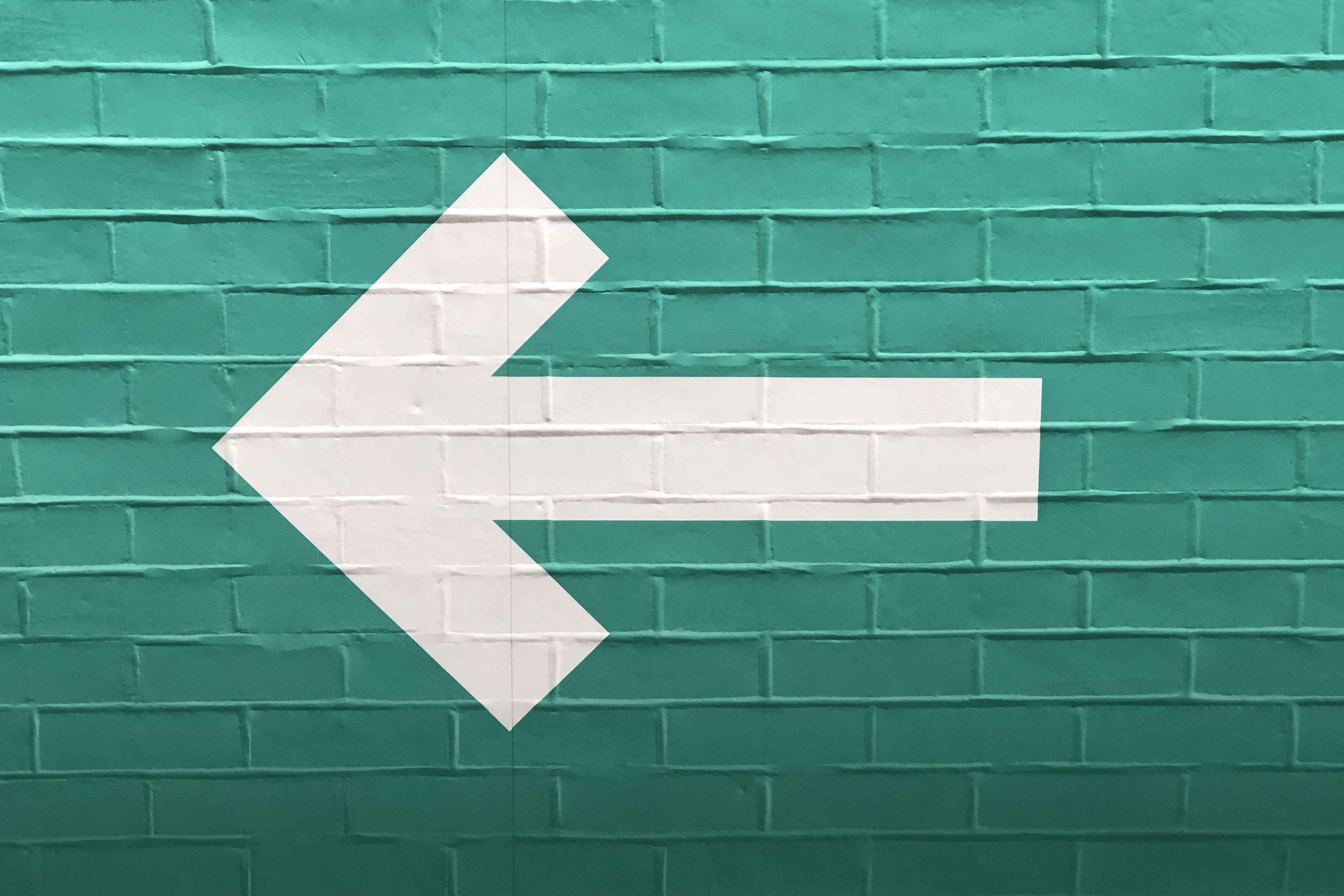 """Further to me posting a white arrow on a blue wall, pointing right, here is the other, a white arrow on a green wall, pointing left."""