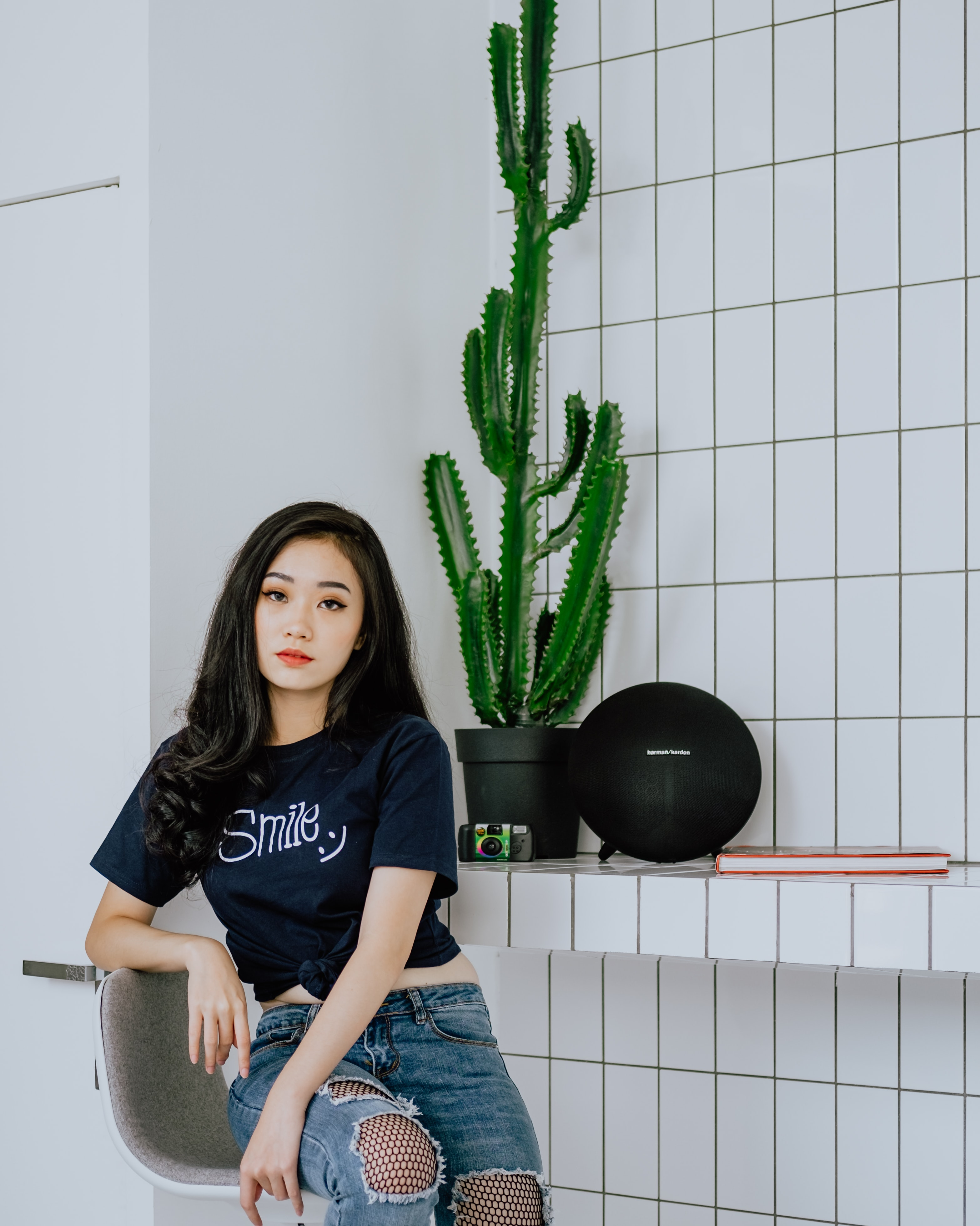 woman sitting on chair beside potted cactus