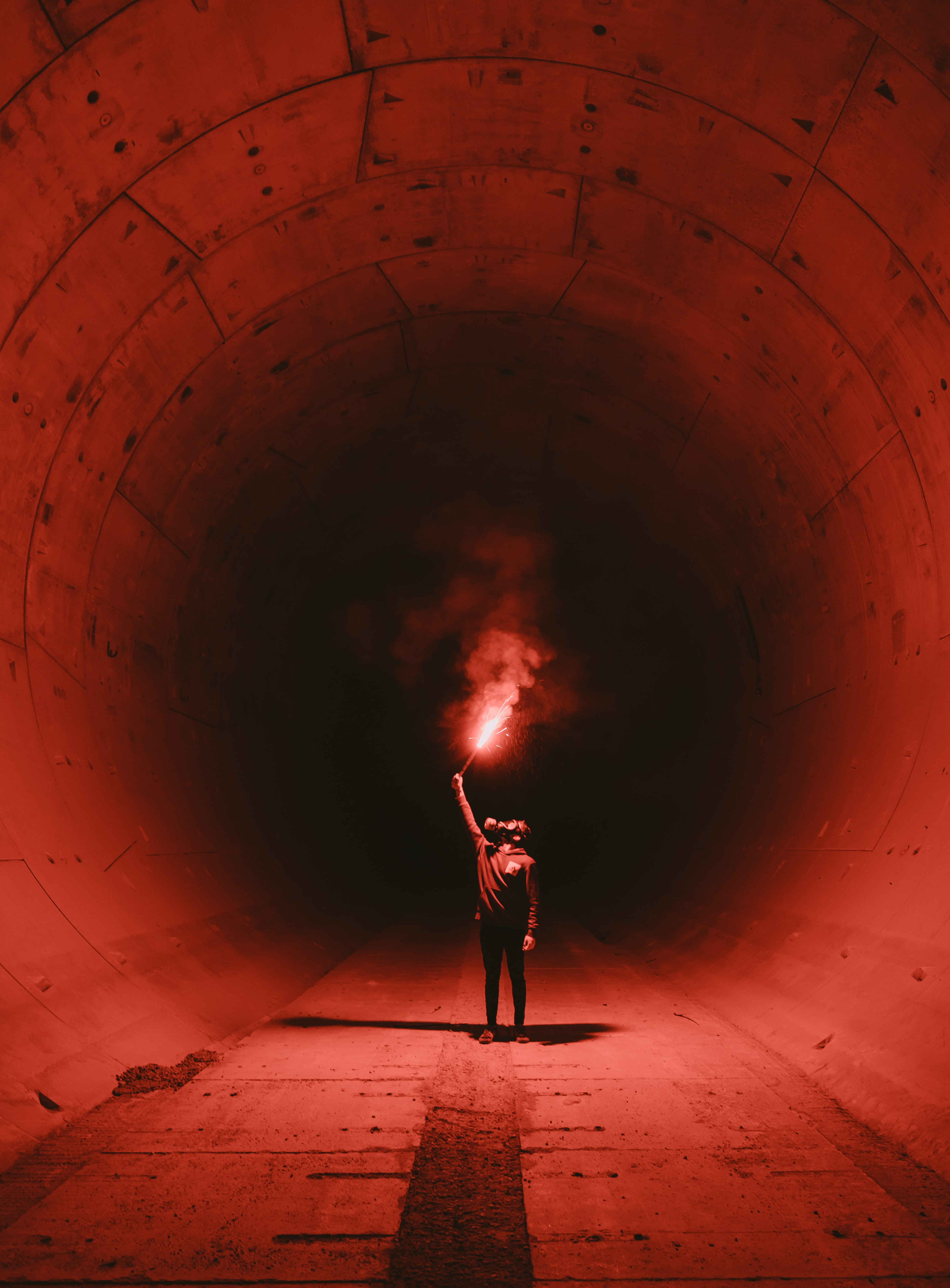 man wearing gas mask holding torch inside tunnel