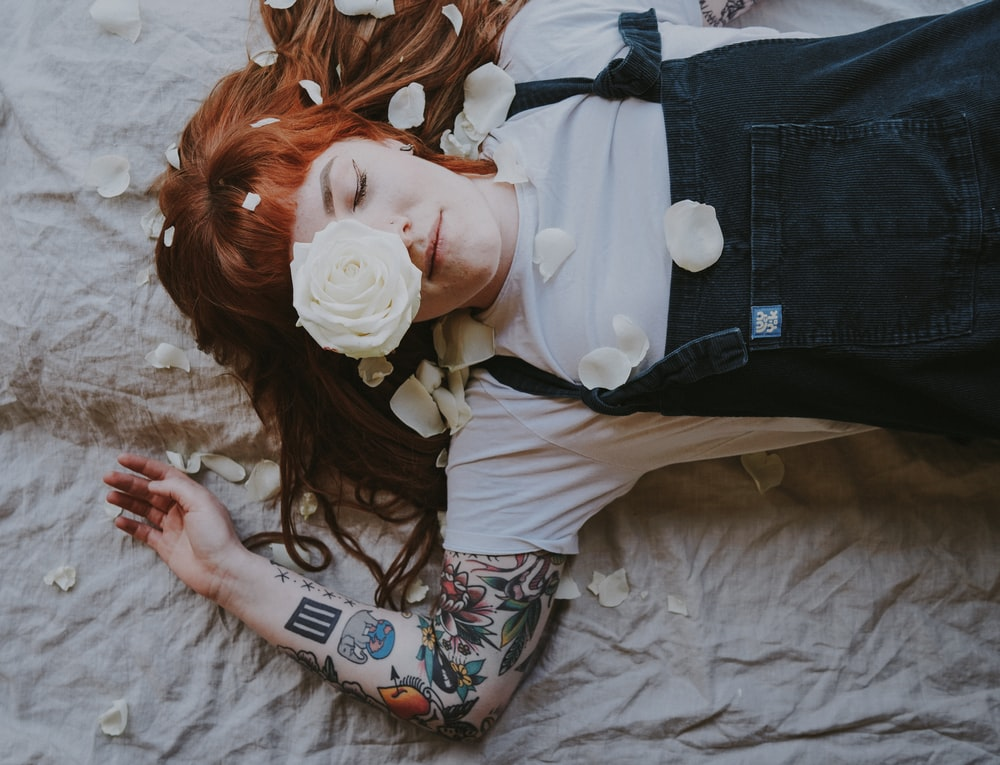 woman with tattoo laying on gray textile with white roses