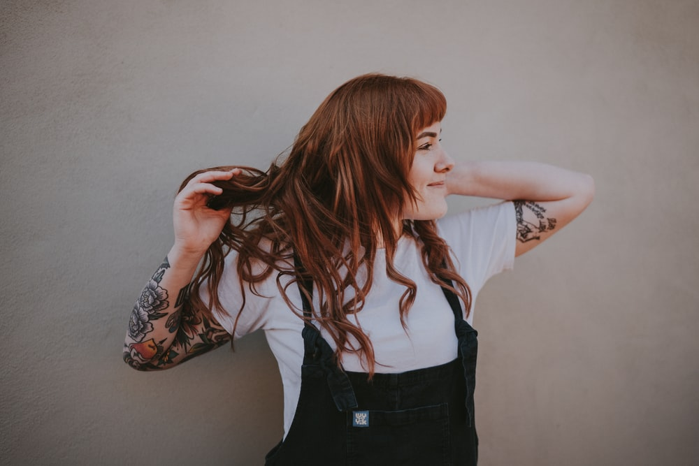 woman holding her hair standing against gray wall
