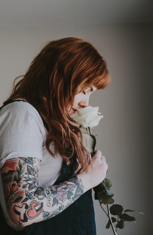 man smelling white rose flower