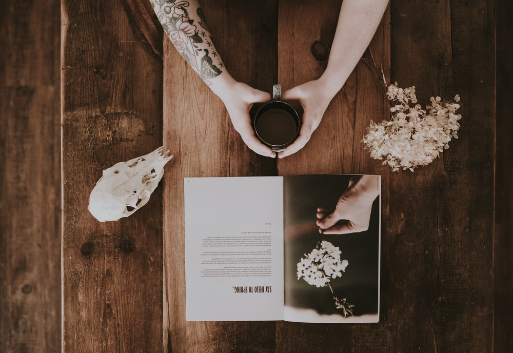 person holding cup with beverage beside white flowers and magazine flat lay photography